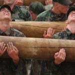 Military recruits holding a log