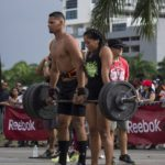 man and woman lifting a barbell