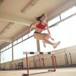 Woman jumping over a hurdle